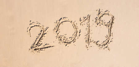 Happy New year 2019 Written on sand white on the  beach Travel and vacations Celebration Shoot photo by smart phone