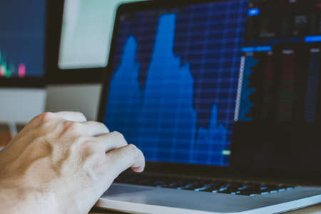 Hand of businessman pointing and look directions change Average line Share price movement Stock trading in the up and down. On the display screen Computer.
