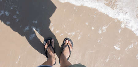 Close up of man in Black slippers feet standing at the beach, with a wave of foaming gentle beneath them.Top view
