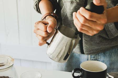 Nahaufnahme, Barista dampft, Milchaufschäumer Latte Art im Kaffeebecher morgens zu Hause. Standard-Bild