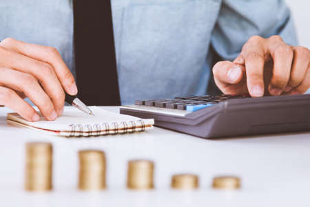 businessman hand using calculator Calculating bonus(Or other compensation) to employees to increase productivity.Writing paper on desk. Banco de Imagens