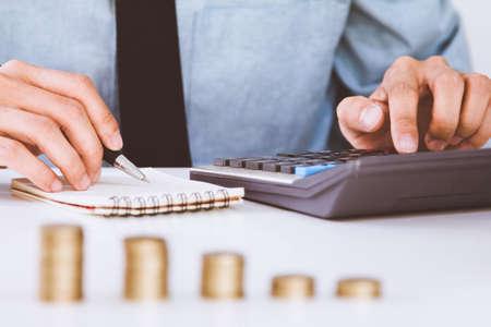 Mano de hombre de negocios con calculadora Calculando bonificación (u otra compensación) a los empleados para aumentar la productividad. Papel de escribir en el escritorio. Foto de archivo