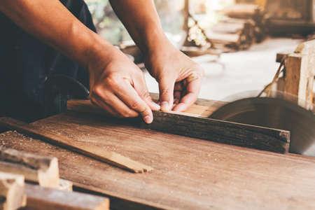 Close-up Man of Carpenters używający piły tarczowej do cięcia małych drewnianych płyt. Koncepcja małej firmy