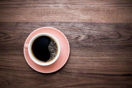 Heißer Kaffee der Tasse trendige Farbe des Jahres 2019 lebende Koralle. Auf Holzuntergrund Standard-Bild