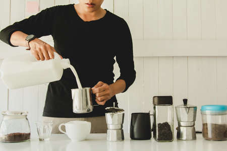 Asian man of Barista is pouring milk latte art in coffee mug. at home in the morning