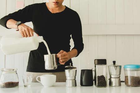 Aziatische man van Barista giet melk latte kunst in koffiemok. 's ochtends thuis