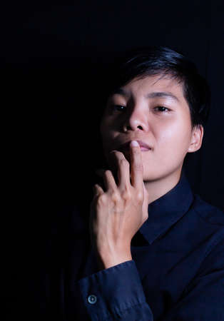 Studio portrait of a Thai Asian LGBT,women handsome beautiful young man  standing on black backdrop is black shirt with feeling,think on face.