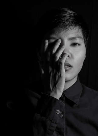 Studio portrait of a Thai Asian LGBT,women handsome beautiful young man  standing on black backdrop is blue shirt with feeling,think on face. black and white photo