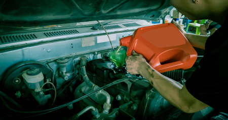 Mechanic Repairman is pouring change engine oil at workshop