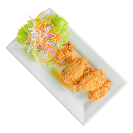 Fried chicken, fish sauce and lettuce, carrots, cauliflower, slide in a white plate isolated white background