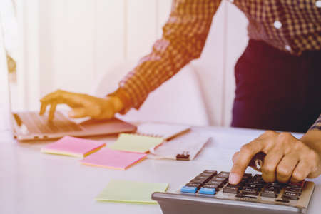 Group businessman hands using calculator Calculating bonus (Or other compensation) to employees to increase productivity