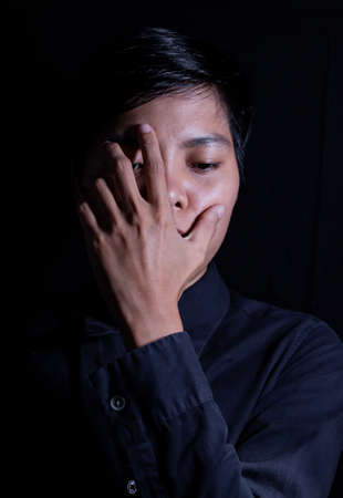 Asian men aged 21-29 years old Made his face sad and covered his eyes in the black background