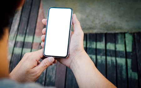 Businessman  hands holding mobile phone with white blank copy space for your text message at cafe  with light Sunset,Vintage tone.Selective focus