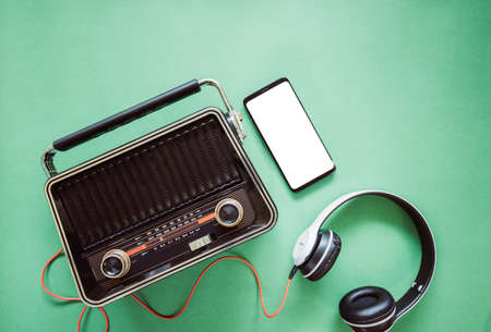 Retro style old boombox radio from 1950s, 1960s and headphones, technology mobile phone blank white space for your text on green pastel paper background 免版税图像