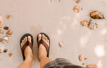Blurred man in Black slippers flip flop feet standing on the beach with a wave of foaming gentle beneath them.Top view