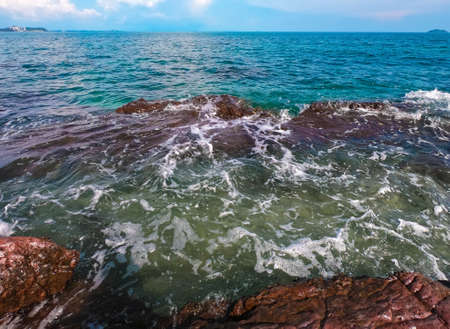 aqua sea water surface waves white Red rocks on white sandy beaches and clouds  natural blue sky. summer vacations at Samed island Rayong Thailand.