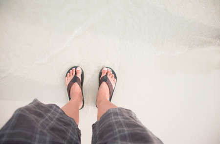 man in Black slippers  flip flop feet standing on the beach with a wave of foaming gentle beneath them.Top view