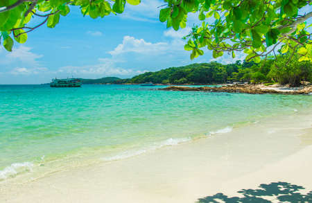 The waves of the sea surface are beautiful clean bright color sandy beach and white clouds the blue sky has a frame with green leaves summer nature at Samet Island Rayong Thailand. Holiday background Imagens
