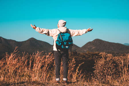 Blurred soft focus, Asian young man in long shirt and gray hat  Carrying backpack hiking standing open arm happy at mountain peak above clouds and blue sky Hiker outdoor. Lamphun Province in morning