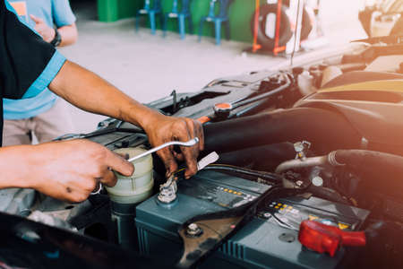 Mechanics use a wrench tool for changing car batteries. Fixing the car concept