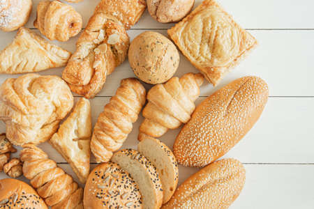 Fresh fragrant baked bread, pie, bread rolls and white sesame on wooden table background, top view copy space for text.