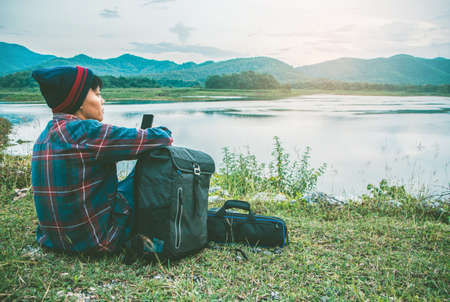 Asian man relaxing in a bag on green grass camping travel vacations in mountains and river Lifestyle concept adventure outdoor wild nature