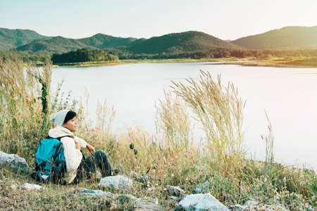 Smiling Asian young man backpackers sitting on the grass in mountains, river enjoying their alone outdoor active. lifestyle travel adventure, people hiking vacations in Thailand Reklamní fotografie