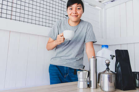 Portrait of Asian young man smiling he holds a cup of hot coffee with equipment tool coffee, maker on the table in the white kitchen in the morning at home.