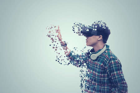 Asian man wearing glasses of virtual reality dissolving into pixels is touching on gray background Future Technology Concept Banco de Imagens