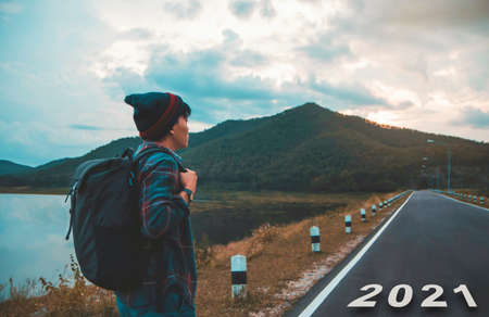 2021 symbolizes the start of the new year. Start of backpacker stand Hiking ready to go on the street at mountains surrounded natural scenery and adventure new normal life Travel alone. Goal of Success