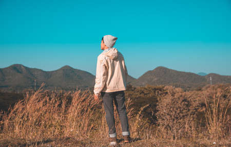 Blur, Asian man Turn around in Long-sleeved shirt and grey hat hiking standing at mountain peak above clouds Hiker outdoor. Maetip Reservoir Lamphun Province, Northern Thailand Province in the morning Stock Photo