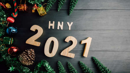 happy New Year 2021 symbol decor ball and a golden bell, pine tree on black wood. Top view 版權商用圖片