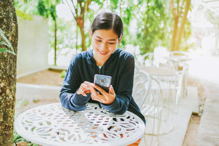Smile Asian young woman using smartphone cell at a coffee shop outdoor