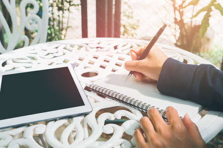 close up Hand of a woman writing homework Online learning on a tablet with a black mock up on the table at  Backyard. Education and learning at home 版權商用圖片