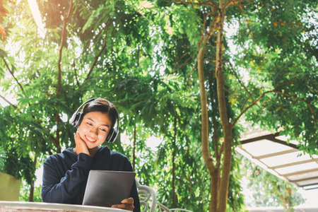 Smile Asian young woman listening Online learning on a tablet at her sitting Backyard,  spending time at home outdoor. 版權商用圖片