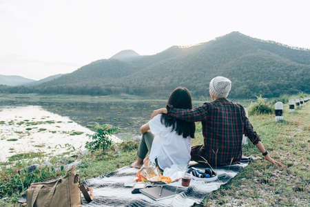 romantic friends looking view of sunset river, dinner together drinking sparkling water and snack. Same-sex young girl couple  sitting on Carpet  in the evening at park nature relax travel holiday 版權商用圖片