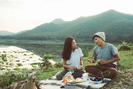 Happy friends having dinner together drinking sparkling water and snack. Same-sex young girl  couple talking sitting on Carpet  in the evening at park nature relax travel holiday