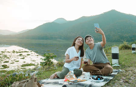 happiness moments romantic friends using smartphone devices take a photo of a couple with a sunset river. Same-sex young girl sitting on Carpet  in the evening at park nature relax travel holiday