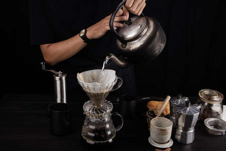 Hand-poured water of dripping coffee on the cup with equipment, tool brewing on the bar at kitchen home 版權商用圖片