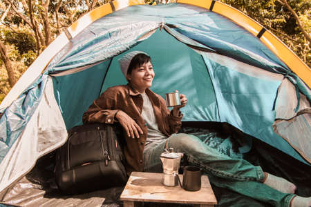 Asian people tourist sitting in touristic tent with cup of hot coffee drinking on the morning. vacation concept
