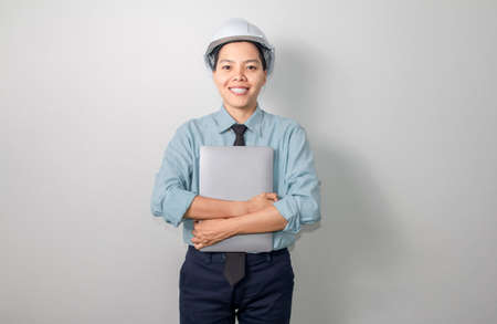 Smile asian engineer wearing a helmet with laptop standing on grey background