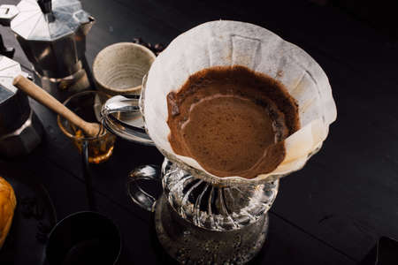 Close up. roasted coffee on coffee percolator with professional of a barista making coffee for dripping hot coffee into the cup with equipment, tool brewing at kitchen home