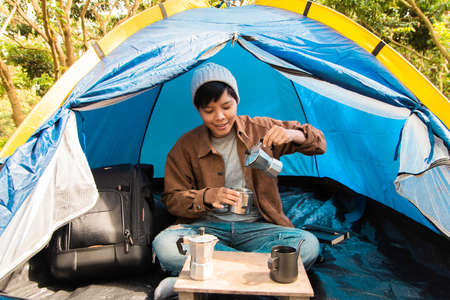 Asian people tourist sitting in touristic tent hand pouring coffee into cup drinking on the morning. vacation concept 版權商用圖片