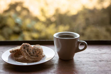 Hot coffee cup of americano, coffee with cookies in a dish on wooden table in the morning. mountain background