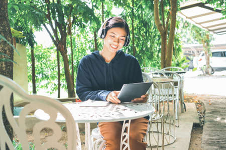 Smiling Asian woman sitting on a chair listening to music and shopping online on a tablet in the park on the morning