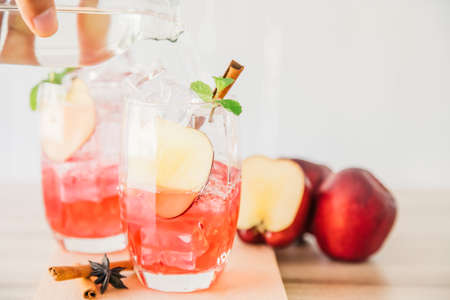 Red apple soda ice in a glass with the herb of cinnamon on wooden background.Copy space for your text