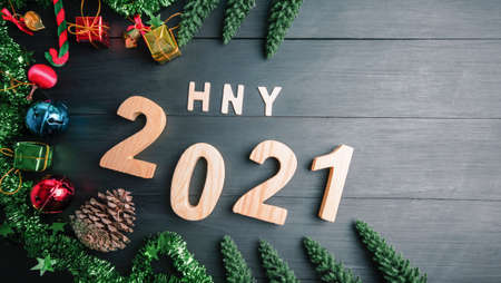 Happy New Year 2021 symbol of 2021 number decor ball and a golden bell, pine tree on black wood. Top view