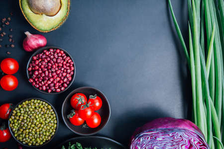 Top view of set vegetables on a black background with Chili, baby carrots, tomatoes, beans, green, red onions, lettuce, pepper, pumpkin, cinnamon, cauliflower, and avocados. copy space for your text