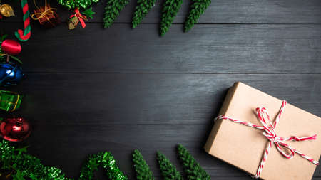 A gift box made of brown paper, tied with a red white bowstring, placed on a wooden board decorated with Christmas trees and colorful bells copy space for text. giving for Holiday, celebration object 版權商用圖片