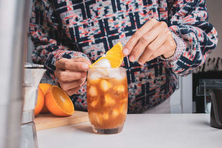 Close up Hand holding slice orange, making a cup of orange juice, black iced coffee homemade with equipment, percolator tool brewing on the table at kitchen home. drink and Food decoration